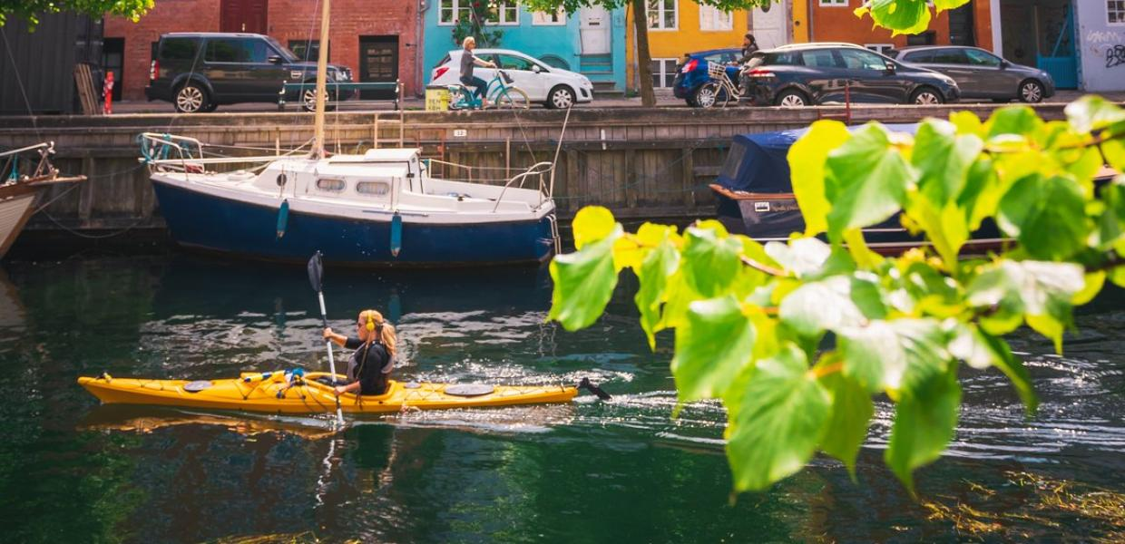 Woman kayaking past coloured houses in Christianshavn