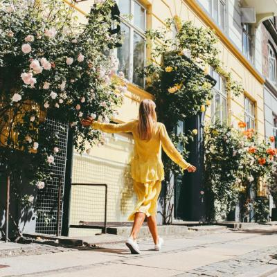 A girl in a yellow dress walks down a rose-lined Copenhagen street